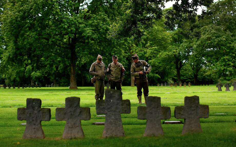 (L-R) Glibert Maugard, Thierry Olewski and Florian Demaux, World War II re-enactors dressed as American soldiers, visit the German War Cemetery which is filled with more the 21,000 German soldiers who died in the Normandy campaign June 3, 2014 in La Cambe, France. June 6th is the 70th anniversary of the D-Day landings which saw 156,000 troops from the allied countries including the United States and the United Kingdom join forces to launch an attack on the beaches of Normandy, these assaults are credited with the eventual defeat of Nazi Germany. A series of events commemorating the 70th anniversary is planned for the week with many heads of state traveling to the famous beaches to pay their respects to those who lost their lives. Photo: Win McNamee, Getty Images / 2014 Getty Images