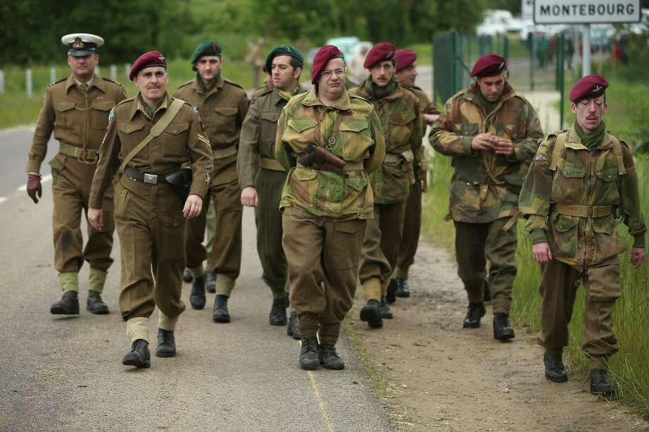 Historical D-Day re-enactment enthusiasts from Italy dressed as Allied soldiers march to a re-enactment camp on June 4, 2014 in Sainte Mere Eglise, France. Friday the 6th of June is the 70th anniversary of the D-Day landings that saw 156,000 troops from the Allied countries, including the United Kingdom and the United States, join forces to launch an audacious attack on the beaches of Normandy,  these assaults are credited with the eventual defeat of Nazi Germany. A series of events commemorating the 70th anniversary are planned for the week with many heads of state traveling to the famous beaches to pay their respects to those who lost their lives. Photo: Sean Gallup, Getty Images / 2014 Getty Images