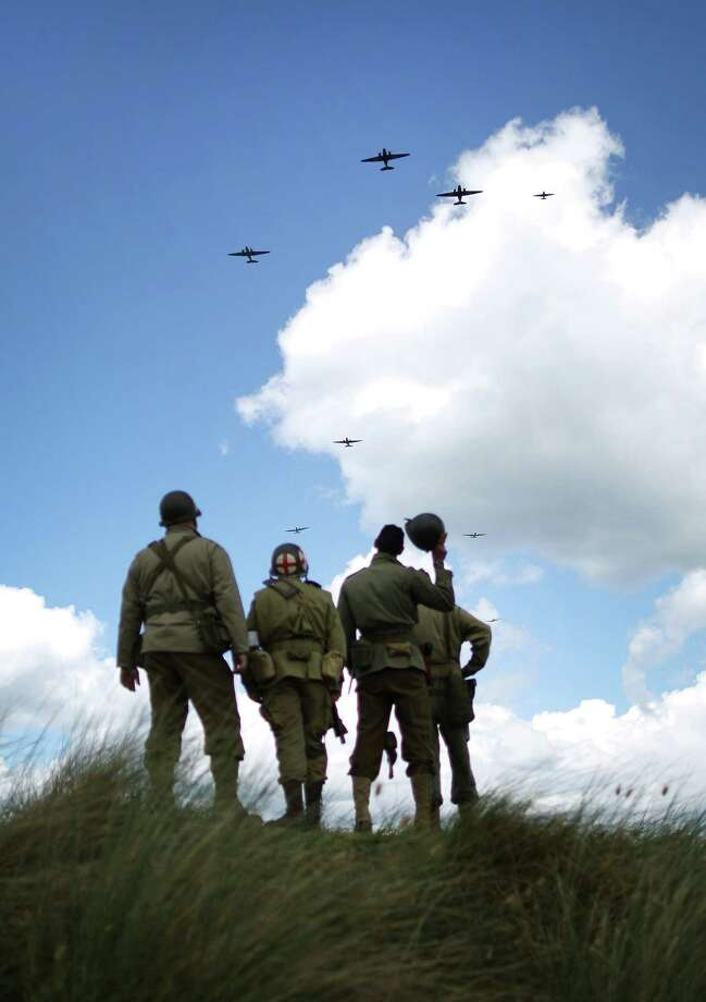 Italian and British military enthusiasts watch from Utah beach as Dakota aircraft flypast on June 4, 2014 near Saint Marie du Mont, France. Friday 6th June is the 70th anniversary of the D-Day landings which saw 156,000 troops from the allied countries including the United Kingdom and the United States join forces to launch an audacious attack on the beaches of Normandy,  these assaults are credited with the eventual defeat of Nazi Germany. A series of events commemorating the 70th anniversary are planned for the week with many heads of state traveling to the famous beaches to pay their respects to those who lost their lives. Photo: Peter Macdiarmid, Getty Images / 2014 Getty Images