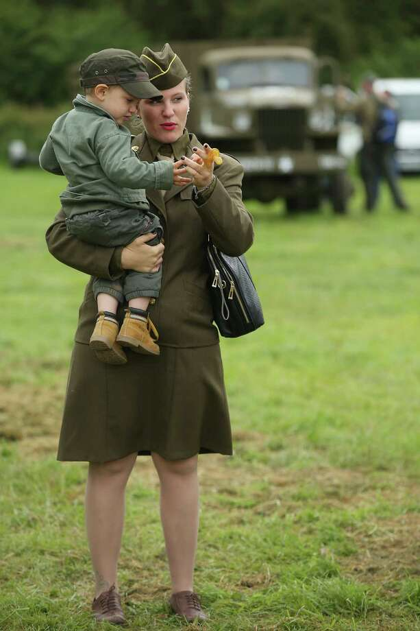 A female historical D-Day re-enactment enthusiast dressed as an American soldier walks with her son at a re-enactment camp on June 4, 2014 in Sainte Mere Eglise, France. Friday the 6th of June is the 70th anniversary of the D-Day landings that saw 156,000 troops from the Allied countries, including the United Kingdom and the United States, join forces to launch an audacious attack on the beaches of Normandy,  these assaults are credited with the eventual defeat of Nazi Germany. A series of events commemorating the 70th anniversary are planned for the week with many heads of state traveling to the famous beaches to pay their respects to those who lost their lives. Photo: Sean Gallup, Getty Images / 2014 Getty Images