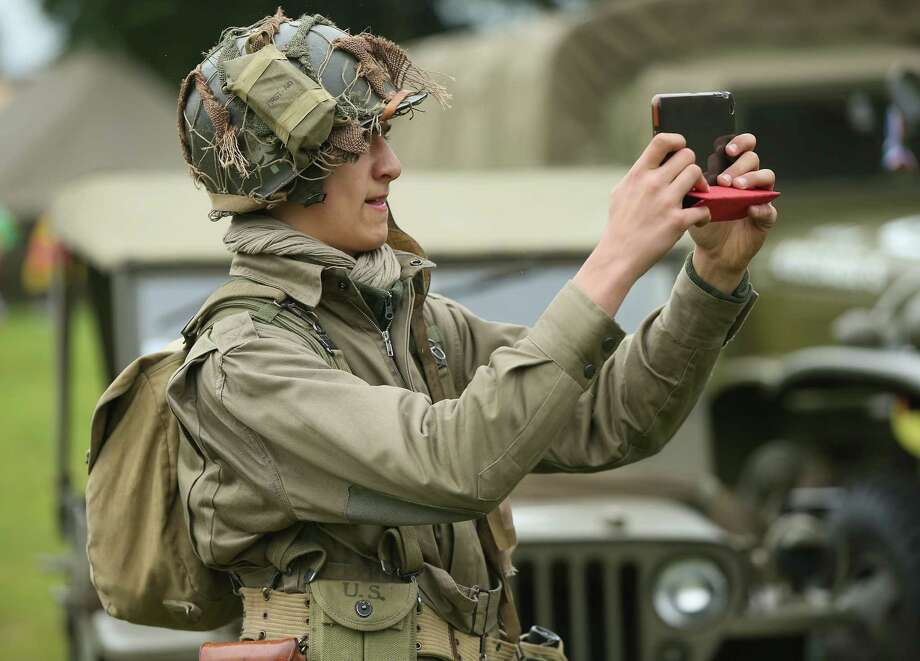 A D-Day re-enactment enthusiast dressed as a World War II American soldier snaps a photo with a mini tablet computer at a re-enactment camp on June 4, 2014 in Sainte Mere Eglise, France. Friday the 6th of June is the 70th anniversary of the D-Day landings that saw 156,000 troops from the Allied countries, including the United Kingdom and the United States, join forces to launch an audacious attack on the beaches of Normandy,  these assaults are credited with the eventual defeat of Nazi Germany. A series of events commemorating the 70th anniversary are planned for the week with many heads of state traveling to the famous beaches to pay their respects to those who lost their lives. Photo: Sean Gallup, Getty Images / 2014 Getty Images