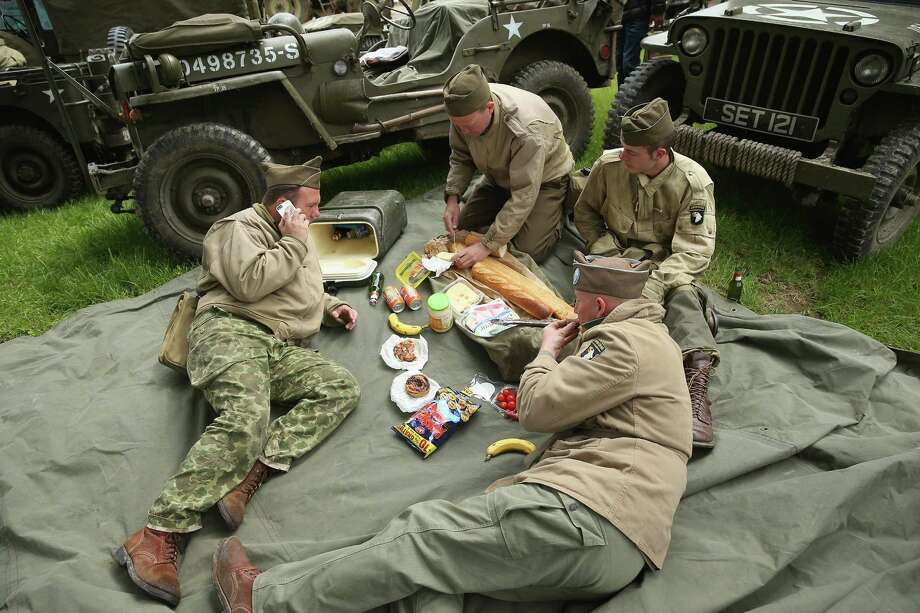 Historical D-Day re-enactment enthusiasts dressed as American soldiers break for lunch amongst their vehicles on June 4, 2014 in Sainte Mere Eglise, France. Friday the 6th of June is the 70th anniversary of the D-Day landings that saw 156,000 troops from the Allied countries, including the United Kingdom and the United States, join forces to launch an audacious attack on the beaches of Normandy,  these assaults are credited with the eventual defeat of Nazi Germany. A series of events commemorating the 70th anniversary are planned for the week with many heads of state traveling to the famous beaches to pay their respects to those who lost their lives. Photo: Sean Gallup, Getty Images / 2014 Getty Images