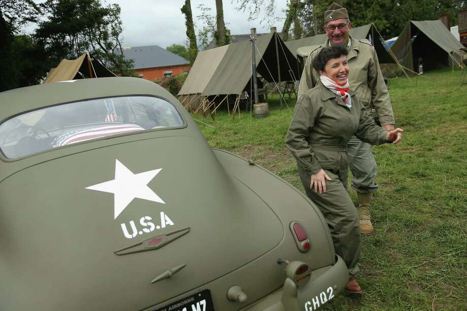 Historical D-Day re-enactment enthusiasts dressed as American soldiers stand next to a Chevrolet de Luxe at a re-enactment camp on June 4, 2014 in Sainte Mere Eglise, France. Friday the 6th of June is the 70th anniversary of the D-Day landings that saw 156,000 troops from the Allied countries, including the United Kingdom and the United States, join forces to launch an audacious attack on the beaches of Normandy,  these assaults are credited with the eventual defeat of Nazi Germany. A series of events commemorating the 70th anniversary are planned for the week with many heads of state traveling to the famous beaches to pay their respects to those who lost their lives. Photo: Sean Gallup, Getty Images / 2014 Getty Images