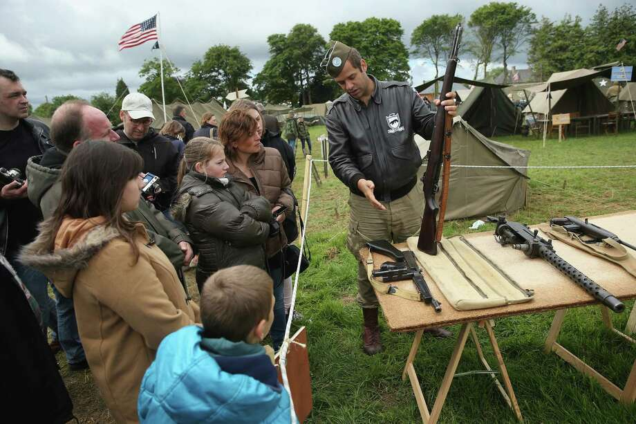 A historical D-Day re-enactment enthusiast dressed as an American soldier explains World War II weapons to visitors at a re-enactment camp on June 4, 2014 in Sainte Mere Eglise, France. Friday the 6th of June is the 70th anniversary of the D-Day landings that saw 156,000 troops from the Allied countries, including the United Kingdom and the United States, join forces to launch an audacious attack on the beaches of Normandy,  these assaults are credited with the eventual defeat of Nazi Germany. A series of events commemorating the 70th anniversary are planned for the week with many heads of state traveling to the famous beaches to pay their respects to those who lost their lives. Photo: Sean Gallup, Getty Images / 2014 Getty Images