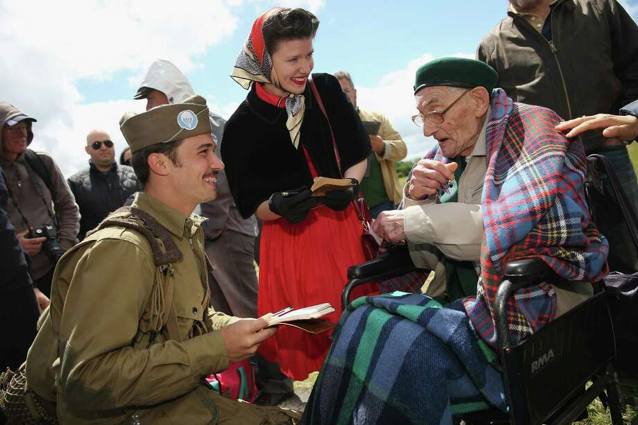 Historical re-enactment enthusiasts and siblings Joshua and Faith Phillips from San Antonio, Texas, chat with Irish World War II veteran Robert McLaughlin, 90, on June 4, 2014 at Carentan, France. McLaughlin was a commando in the Ulster Rifles of the British Army, participated in the capture of Pegasus Bridge during the D-Day invasion in 1944 and is visiting Normandy for the first time since the war. Friday the 6th of June is the 70th anniversary of the D-Day landings that saw 156,000 troops from the Allied countries, including the United Kingdom and the United States, join forces to launch an audacious attack on the beaches of Normandy,  these assaults are credited with the eventual defeat of Nazi Germany. A series of events commemorating the 70th anniversary are planned for the week with many heads of state traveling to the famous beaches to pay their respects to those who lost their lives. Photo: Sean Gallup, Getty Images / 2014 Getty Images