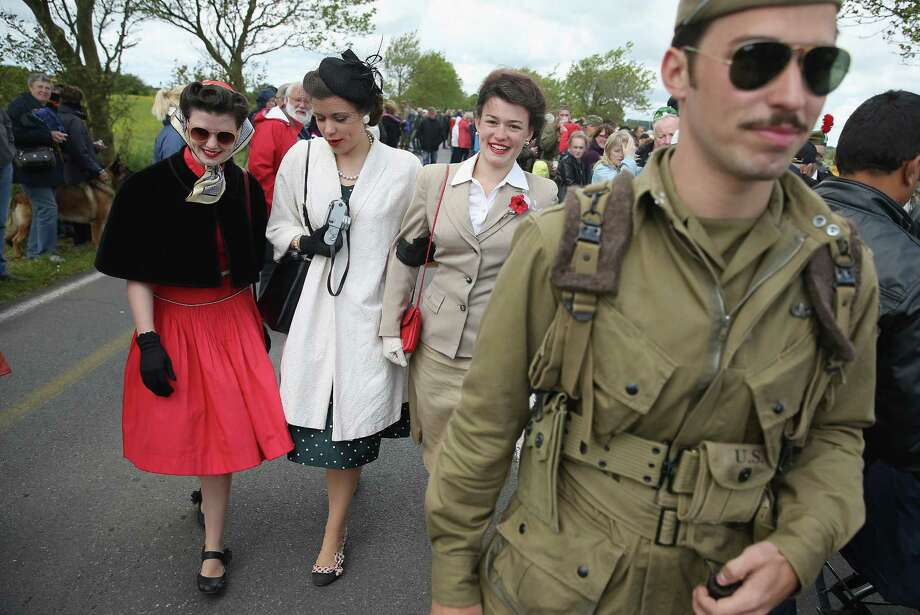 D-Day re-enactment enthusiasts and siblings Faith, Liberty, Jubilee and Joshua Phillips from San Antonio, Texas, attend a planned parachute drop on June 4, 2014 at Carentan, France. Friday the 6th of June is the 70th anniversary of the D-Day landings that saw 156,000 troops from the Allied countries, including the United Kingdom and the United States, join forces to launch an audacious attack on the beaches of Normandy,  these assaults are credited with the eventual defeat of Nazi Germany. A series of events commemorating the 70th anniversary are planned for the week with many heads of state traveling to the famous beaches to pay their respects to those who lost their lives. Photo: Sean Gallup, Getty Images / 2014 Getty Images