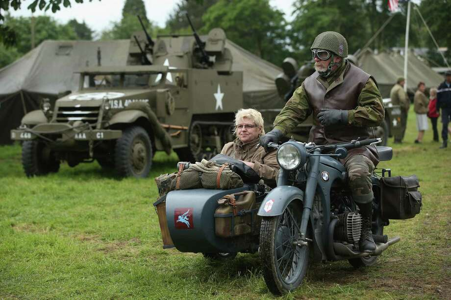 D-Day re-enactment enthusiasts dressed as Allied soldiers ride a World War II-era motorcycle and sidecar through a re-enactment camp on June 4, 2014 in Sainte Mere Eglise, France. Friday the 6th of June is the 70th anniversary of the D-Day landings that saw 156,000 troops from the Allied countries, including the United Kingdom and the United States, join forces to launch an audacious attack on the beaches of Normandy,  these assaults are credited with the eventual defeat of Nazi Germany. A series of events commemorating the 70th anniversary are planned for the week with many heads of state traveling to the famous beaches to pay their respects to those who lost their lives. Photo: Sean Gallup, Getty Images / 2014 Getty Images