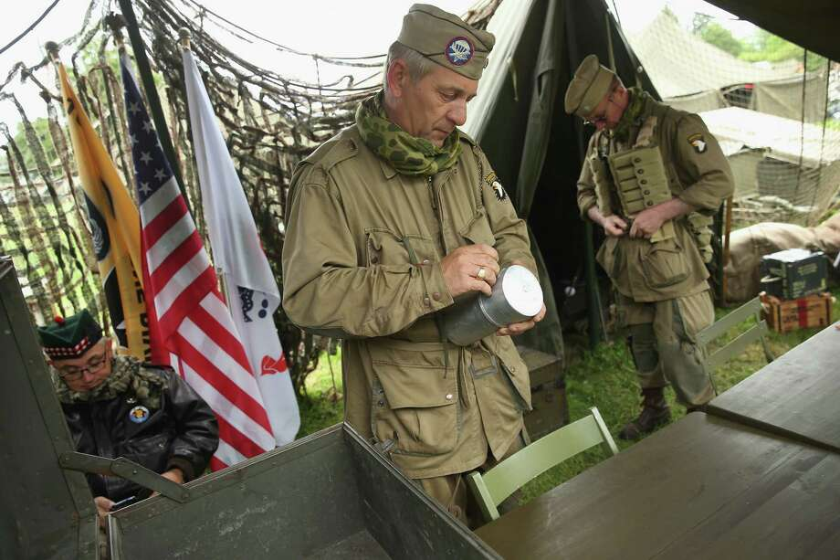 D-Day re-enactment enthusiasts dressed as World War II soldiers from the American 101st Airborne attend a re-enactment camp on June 4, 2014 in Sainte Mere Eglise, France. Friday the 6th of June is the 70th anniversary of the D-Day landings that saw 156,000 troops from the Allied countries, including the United Kingdom and the United States, join forces to launch an audacious attack on the beaches of Normandy,  these assaults are credited with the eventual defeat of Nazi Germany. A series of events commemorating the 70th anniversary are planned for the week with many heads of state traveling to the famous beaches to pay their respects to those who lost their lives. Photo: Sean Gallup, Getty Images / 2014 Getty Images