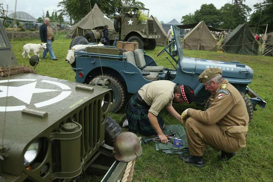 D-Day re-enactment enthusiasts dressed as World War II Allied soldiers attempt to repair a jeep at a re-enactment camp on June 4, 2014 in Sainte Mere Eglise, France. Friday the 6th of June is the 70th anniversary of the D-Day landings that saw 156,000 troops from the Allied countries, including the United Kingdom and the United States, join forces to launch an audacious attack on the beaches of Normandy,  these assaults are credited with the eventual defeat of Nazi Germany. A series of events commemorating the 70th anniversary are planned for the week with many heads of state traveling to the famous beaches to pay their respects to those who lost their lives. Photo: Sean Gallup, Getty Images / 2014 Getty Images