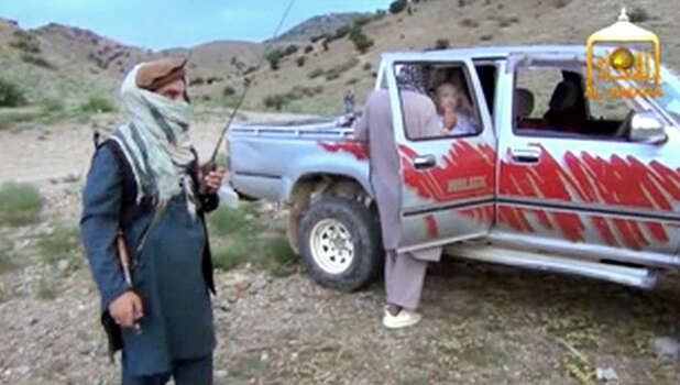 In this image taken from video obtained from Voice Of Jihad Website, which has been authenticated based on its contents and other AP reporting, Sgt. Bowe Bergdahl sits in a vehicle guarded by the Taliban in eastern Afghanistan. The Taliban have released a video showing the handover of Bergdahl to U.S. forces in eastern Afghanistan. The video, emailed to media on Wednesday, shows Bergdahl in traditional Afghan clothing sitting in a pickup truck parked on a hillside. More than a dozen Taliban fighters with machine guns stand around the truck and on the hillside. Photo: Uncredited, AP / Voice Of Jihad Website