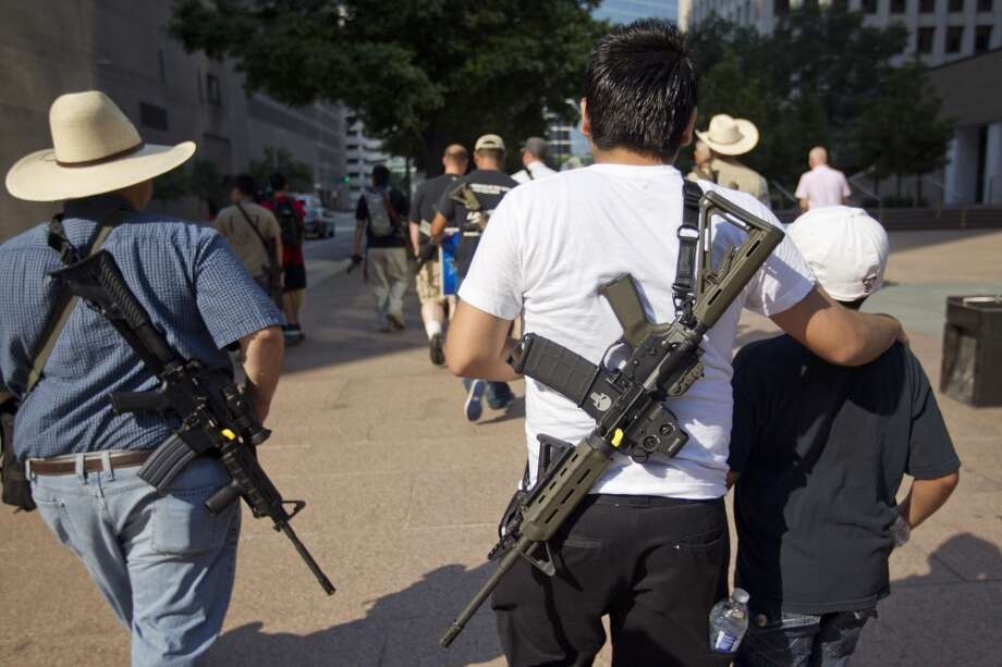 "Jr. Velez, 21, puts his arm around his little brother while walking with his AR-15 rifle down Bagby, as they joined a group of more than 20 people with the pro-gun organization, Come and Take it Houston, as part of a rally to educate people about local gun laws Thursday, July 4, 2013, in Houston.  ""This is a Come and Take it Houston walk to help inform citizens about the gun laws here in Texas,"" co-organizer Kenneth Lindbloom said. ""In Texas there are no restrictions on the open cary of long arms like rifles and shotguns. We want people to realize that in the hands of good people, guns are not dangerous and they don't kill people. When good people have guns it serves as a deterrent to stop crime.""( Johnny Hanson / Houston Chronicle ) Photo: Houston Chronicle"