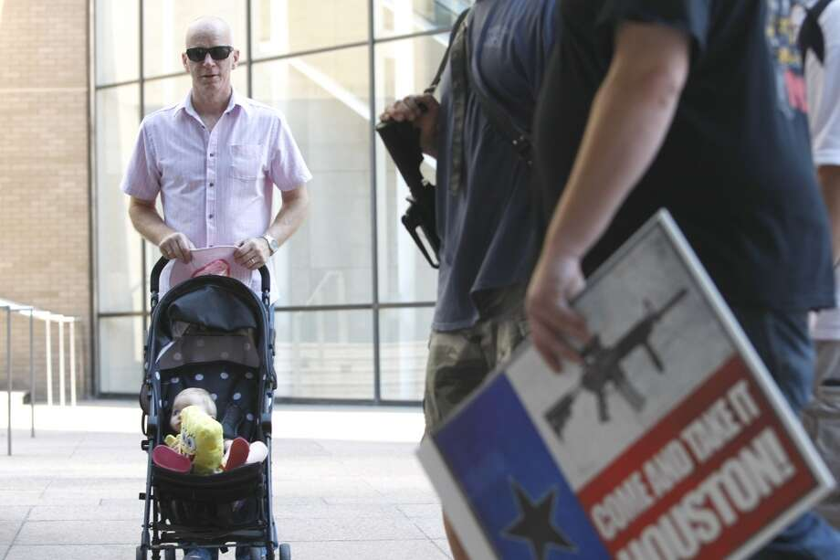 "Neil Darlington from Chester, England watched with his 11-month-old daughter Chrystal, as a group of about 25 people with the organization pro-gun rights organization, Come and Take it Houston, walked through downtown carrying their guns as part of a rally to educate people about gun laws Thursday, July 4, 2013, in Houston.  âÄúTo walk the streets and see people with shotguns and ammo is a bit different,âÄù Darlington said. âÄúItâÄôs a completely different culture. We are use to seeing police with guns, but not that.âÄù ""This is a Come and Take it Houston walk to help inform citizens about the gun laws here in Texas,"" co-organizer  Kenneth Lindbloom said. ""In Texas there are no restrictions on the open cary of long arms like rifles and shotguns and we want people to realize that in the hands of good people, guns are not dangerous and they don't kill people. When good people have guns it serves as a deterrent to stop crime.""( Johnny Hanson / Houston Chronicle ) Photo: Houston Chronicle"