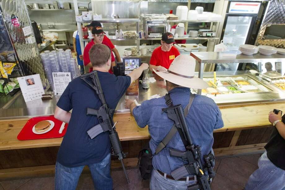 Members of the gun rights group Come and Take it Houston get lunch at Tony's BBQ & Steak House, which they say is a gun-friendly establishment, after walking with their guns through downtown Houston as part of a pro-gun rally on Thursday, July 4, 2013. (AP Photo/Houston Chronicle, Johnny Hanson) Photo: Associated Press