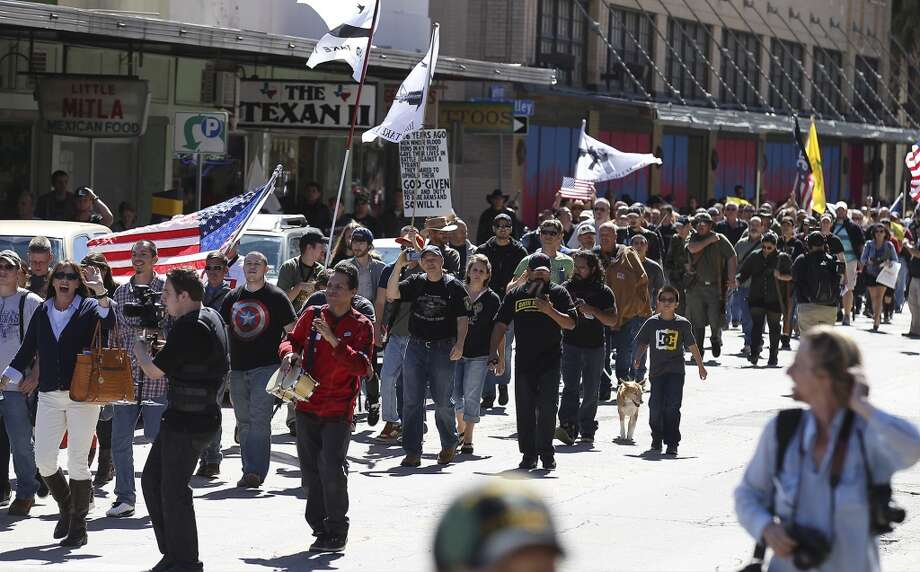 Gun owners march toward Travis Park as part of the Come And Take It San Antonio pro-gun rally on Saturday, Oct. 19, 2013. Several hundred pro-gun owners displayed their rifles and long arms at a rally on the grounds of the Alamo. The group later marched to Travis Park where the event concluded. (Kin Man Hui/San Antonio Express-News) Photo: San Antonio Express-News