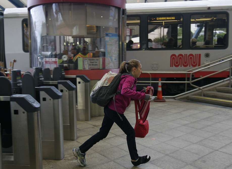 A passenger runs to catch an inbound streetcar at the West Portal Station on the third day of a sickout by Muni employees in San Francisco on Wednesday. Photo: Paul Chinn, The Chronicle
