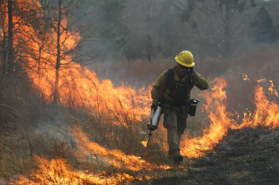 A firefighter at a controlled burn works on fire suppression techniques. Photo: Texas A&M Forest Service