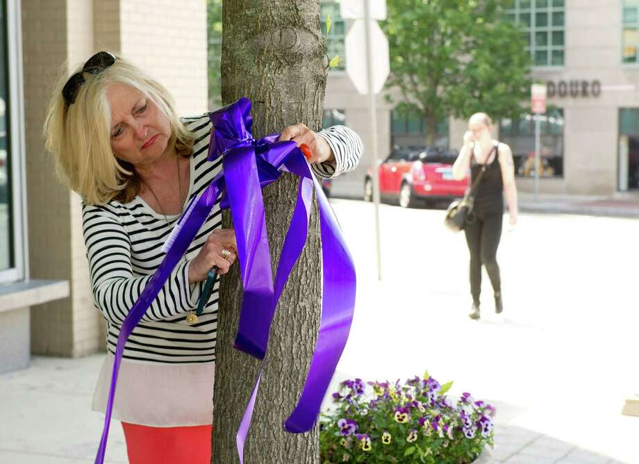 Sandy Ceppos of Westport, Marketing Director for Mitchell's family stores and Celebrating Hope committee member, helps tie purple ribbons to the trees along Greenwich Ave. on Wednesday, June 4, 2014, to raise awareness for Alzheimer's Disease and the upcoming cocktail party to benefit the Connecticut Chapter of the Alzheimer's Association. Photo: Lindsay Perry / Stamford Advocate