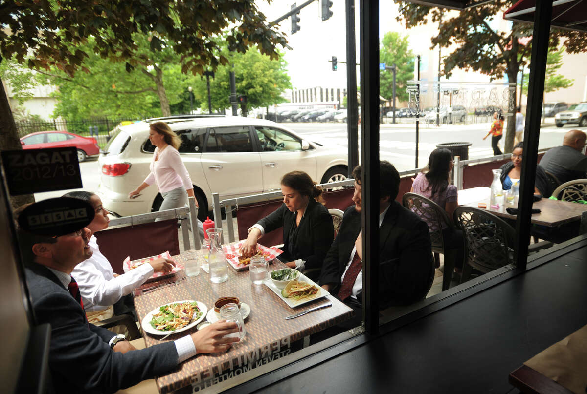 Diners enjoy sidewalk seating outside the Barnum Publick House restaurant at 1020 Broad Street in downtown Bridgeport, Conn.