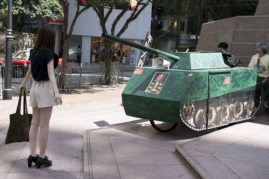 """TOPSHOTS A young woman reenacts the famous """"Tank Man"""" scene from the 1989 Tiananmen Square military crackdown on pro-democracy protesters om Beijing, in front of a replica of a Chinese tank in Hong Kong on June 4, 2014. Up to 200,000 people were set to take part in a candlelight vigil in Hong Kong on June 4 to commemorate the 25th anniversary of the bloody Tiananmen Square crackdown, as China seeks to wipe the incident from memory.  AFP PHOTO / ALEX OGLEAlex Ogle/AFP/Getty Images Photo: Alex Ogle, AFP/Getty Images"""