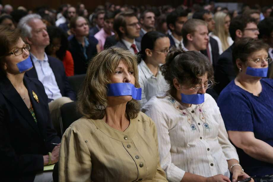 """The silent minority:Four women wear tape over their mouths as a protest for campaign finance reform during a Senate hearing on political donations and freedom of speech in Washington. Liberal political groups delivered 2 million petitions calling for """"... a proposed constitutional amendment to restore the ability of Congress and the states to regulate the raising and spending of money in elections."""" Photo: Chip Somodevilla, Getty Images"""