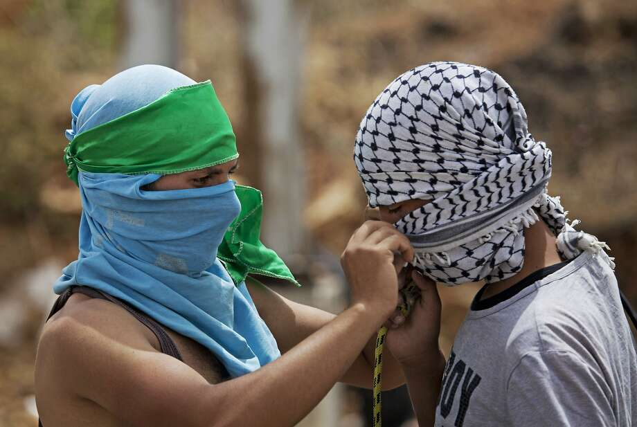 Once enemies, now dressing each other: A Palestinian wearing the green headband of Hamas helps a fellow protester cover his face with the black-and-white scarf representing the Fatah movement outside an Israeli military prison near Ramallah, West Bank. Hamas and Fatah have been longtime rivals, but earlier this week formed a unity government, signaling an end to a seven-year split. Photo: Majdi Mohammed, Associated Press