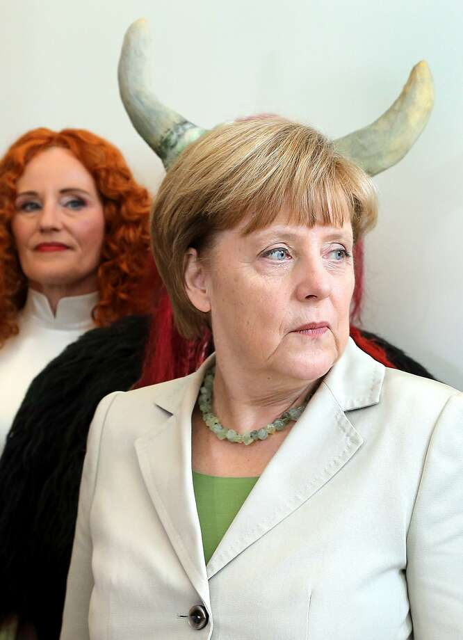 Wagner's new Brunhilde: The horns growing from Chancellor Angela Merkel's head are actually part of helmet worn by an obscured actor at Uckermaerkische Buehnen Schwedt theater in Berlin. The actors invited the chancellor to attend the open-air fantasy festival Der Fluch der Weissen Frau (The Bane of the White Woman). Photo: Wolfgang Kumm, AFP/Getty Images