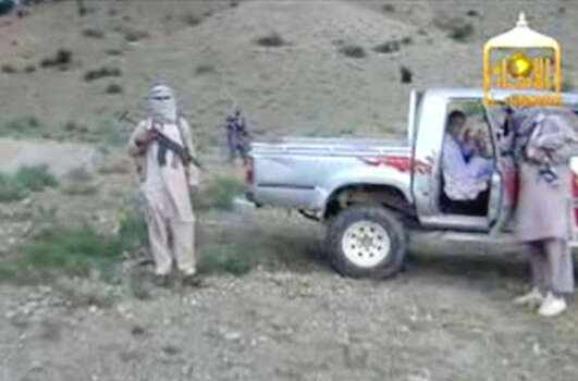 In this image taken from video obtained from the Voice Of Jihad Website, which has been authenticated based on its contents and other AP reporting, Sgt. Bowe Bergdahl sits in a vehicle guarded by the Taliban in eastern Afghanistan. The Taliban have released a video showing the handover of Bergdahl to U.S. forces in eastern Afghanistan. The video, emailed to media on Wednesday, shows Bergdahl in traditional Afghan clothing sitting in a pickup truck parked on a hillside. More than a dozen Taliban fighters with machine guns stand around the truck and on the hillside. Photo: Uncredited, AP / Voice Of Jihad Website
