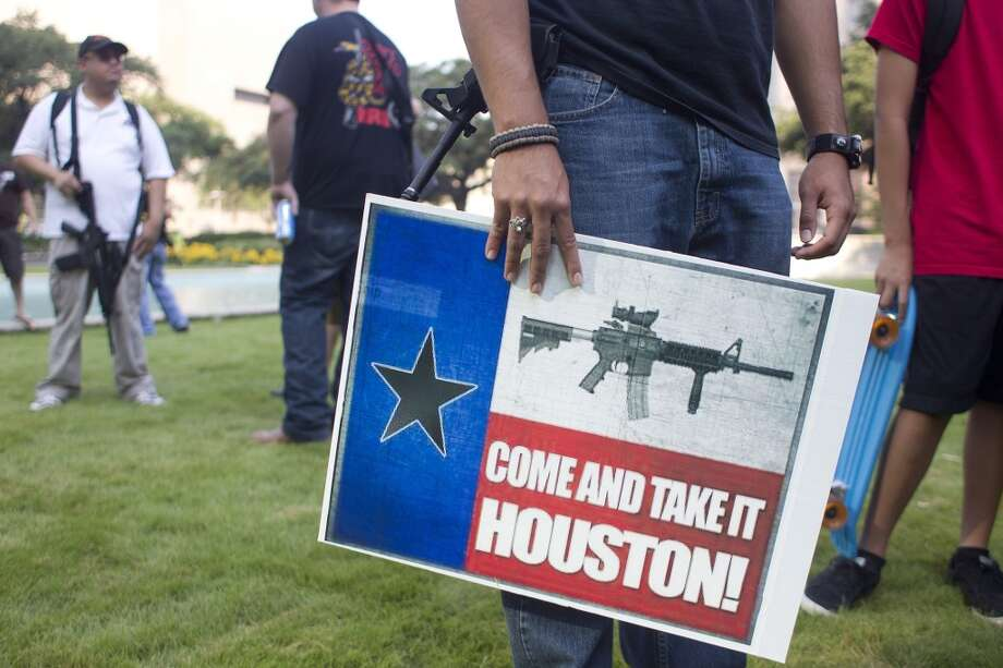 """WIth guns in hand, a group of more than 20 people with the pro-gun organization, Come and Take it Houston, assembled at City Hall before walking through downtown carrying their guns as part of a rally Thursday, July 4, 2013, in Houston.  """"This is a Come and Take it Houston walk to help inform citizens about the gun laws here in Texas,"""" co-organizer  Kenneth Lindbloom said. """"In Texas there are no restrictions on the open cary of long arms like rifles and shotguns. We want people to realize that in the hands of good people, guns are not dangerous and they don't kill people. When good people have guns it serves as a deterrent to stop crime.""""( Johnny Hanson / Houston Chronicle ) Photo: Houston Chronicle"""