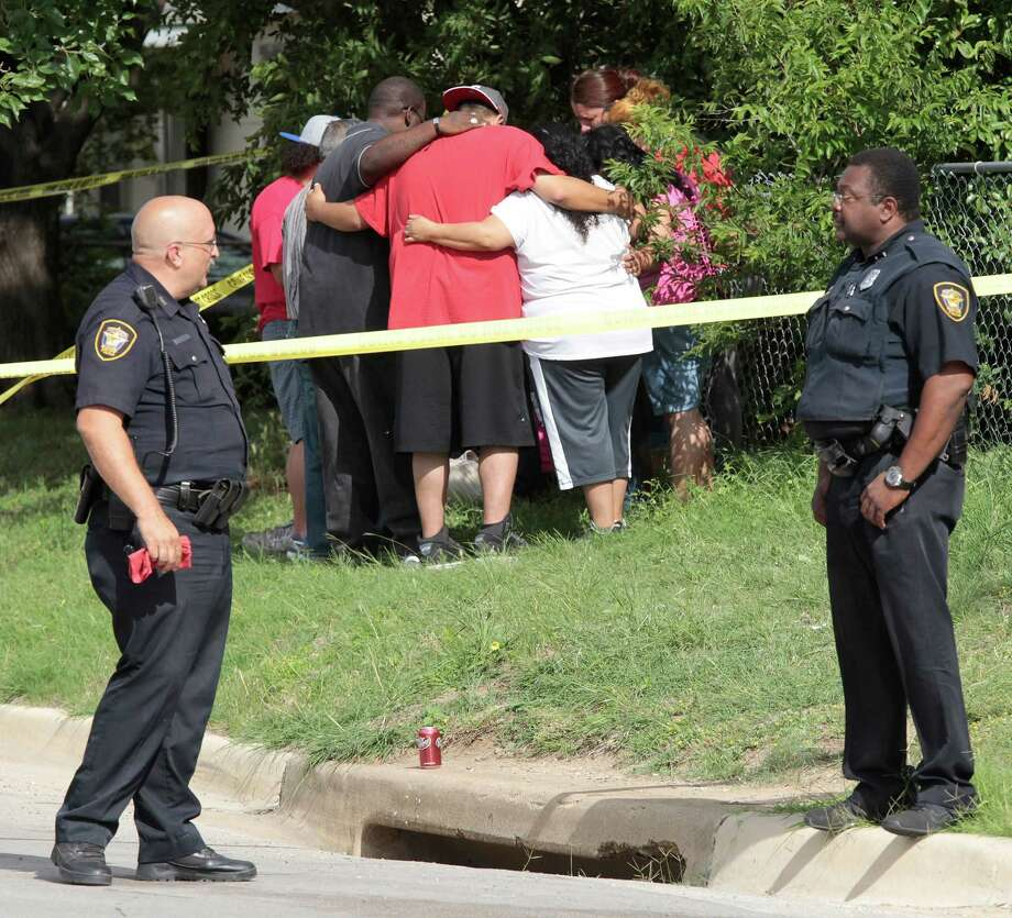 Fort Worth Police stand by as relatives grieve outside a home where three women were found dead in south Fort Worth, Texas, Tuesday, June 3, 2014.  Fort Worth police Sgt. Raymond Bush says officers found multiple bodies around 8 a.m. Tuesday in the single-story home. Bush declined to comment further. Angel Bueno says three women were killed and that he is the nephew of one of the victims, 48-year-old Cynthia Serrano, who raised him. Bueno says the other victims are Serrano's daughter, 21-year-old April Serrano, and Serrano's sister, 35-year-old Cathy de Leon. Bueno says Serrano's husband, James Serrano, called 911 and is being questioned by police. Photo: Ron T. Ennis, AP / The Fort Worth Star-Telegram