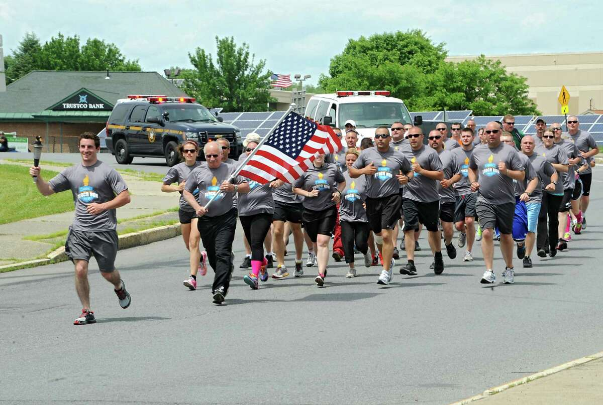 Runners of the third leg of the Law Enforcement Torch Run Series for Special Olympics New York turns onto Main St. to end at the Mechanicville Public Library Wednesday, June 4, 2014, in Mechanicville, N.Y. (Lori Van Buren / Times Union)