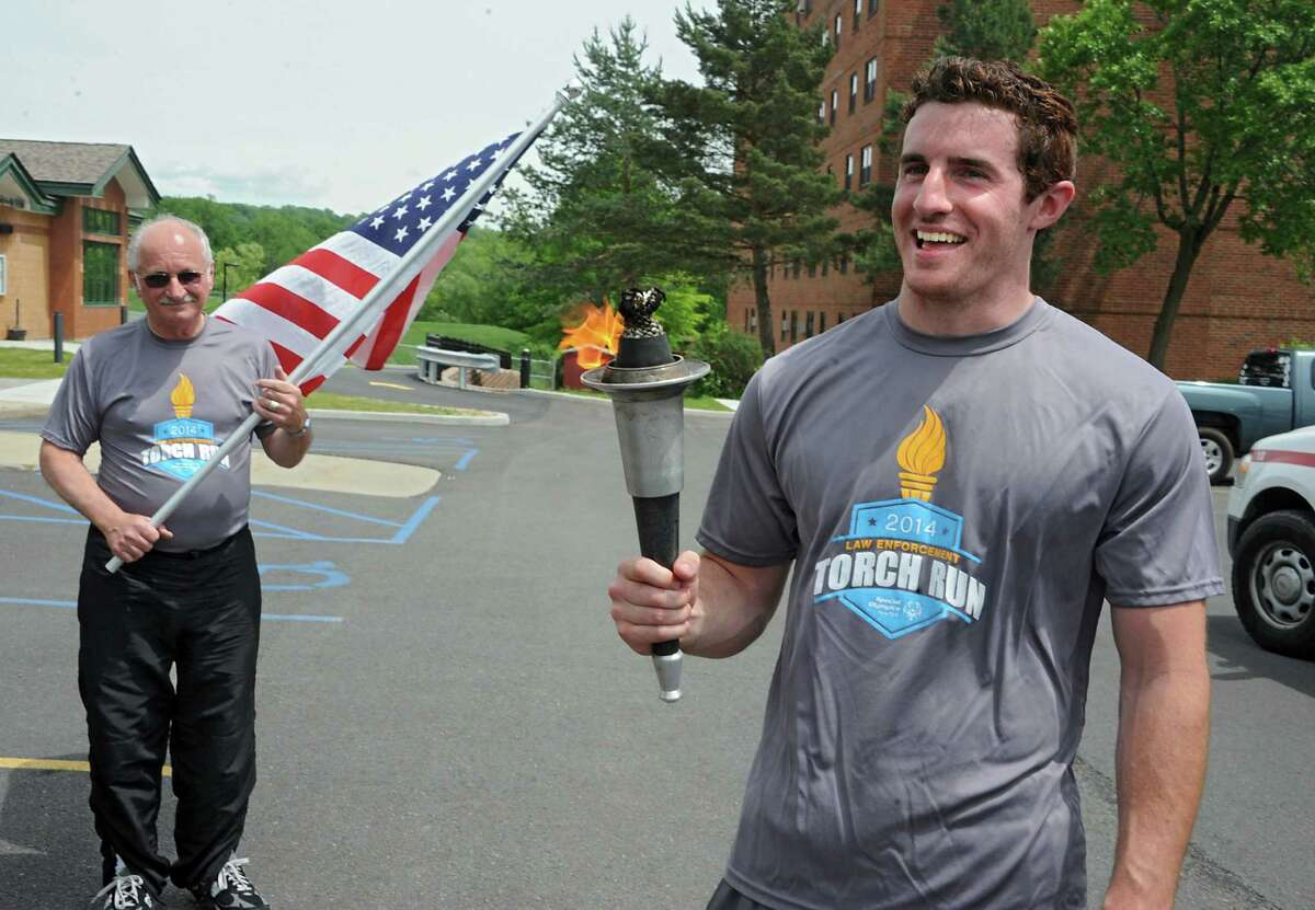 Zachary Bango of Saratoga Springs was the last torch carrier in the third leg of the Law Enforcement Torch Run Series for Special Olympics New York which ended at the Mechanicville Public Library Wednesday, June 4, 2014, in Mechanicville, N.Y. Lindsey Bell of Kingsbury, left, carried the American flag. (Lori Van Buren / Times Union)