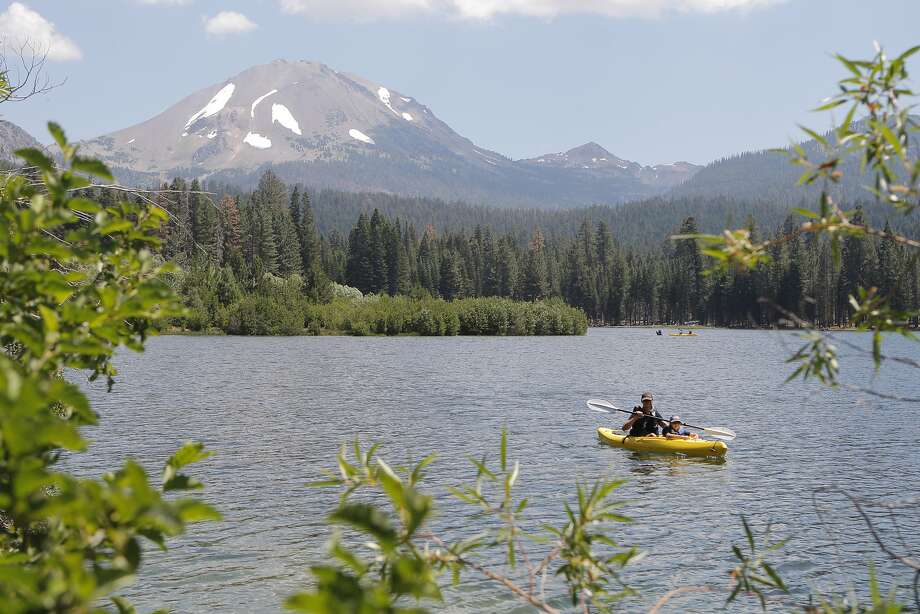 James Speer and James Jr. paddle rental kayak on Manzanita Lake as Lassen Peak looms in distance at Lassen Volcanic National Park~~ Photo: Tom Stienstra