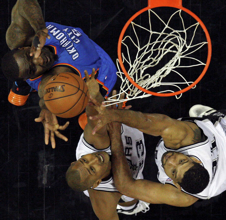Oklahoma City Thunder's Kendrick Perkins, San Antonio Spurs' Boris Diaw and Tim Duncan grab for a rebound during Game 5 of the Western Conference finals Thursday May 29, 2014 at the AT&T Center. The Spurs won 117-89. Photo: Edward A. Ornelas, Staff / © 2014 San Antonio Express-News