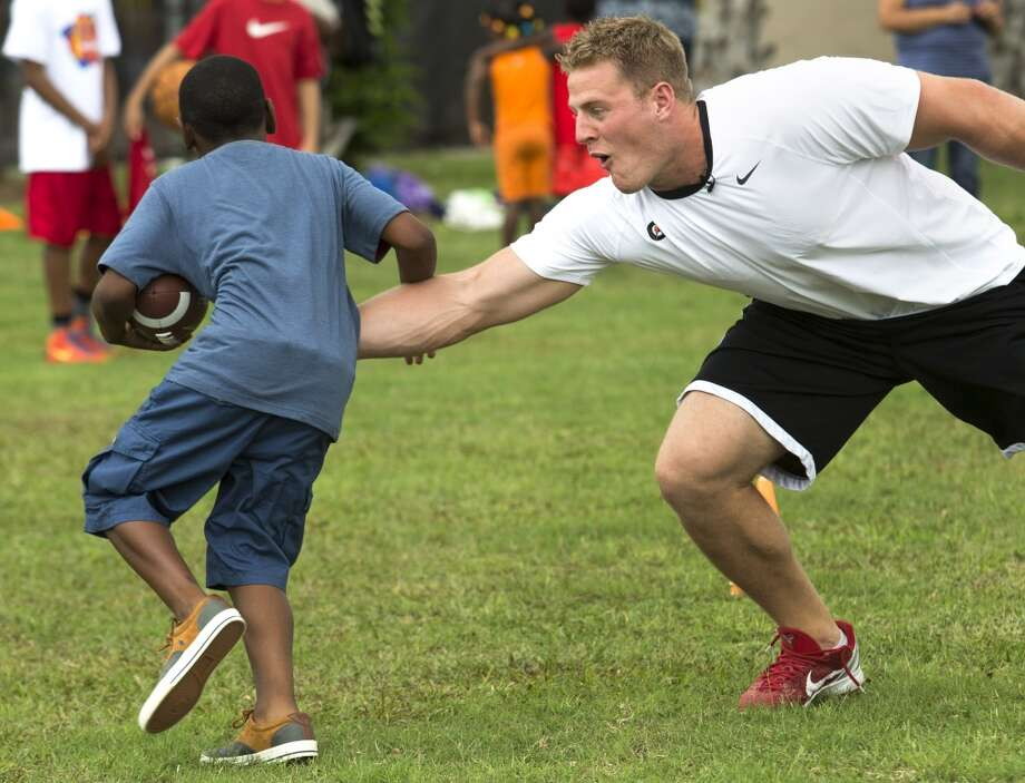 "Texans defensive end J.J. Watt reaches out to ""tackle"" Trayveon Richard as he runs football drills with the children at the Houston Texans YMCA on Wednesday. After Watt ran the children through drills, he stressed the importance of hydration on behalf of the Gatorade Beat the Heat program. He also stressed the importance of listening and following the lead of their parents and mentors. Photo: Brett Coomer , Houston Chronicle"
