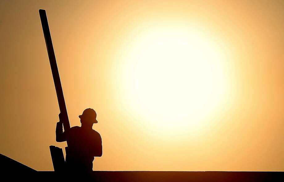 A construction worker is atop a roof at sunrise to beat June's daytime highs around 118 degrees in Queen Creek, Ariz. Photo: Matt York, Associated Press
