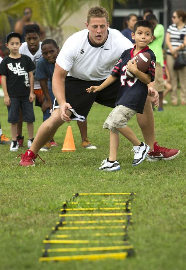"J.J. Watt, left, lines up to ""tackle"" Charles Gonzales. Photo: Brett Coomer , Houston Chronicle"