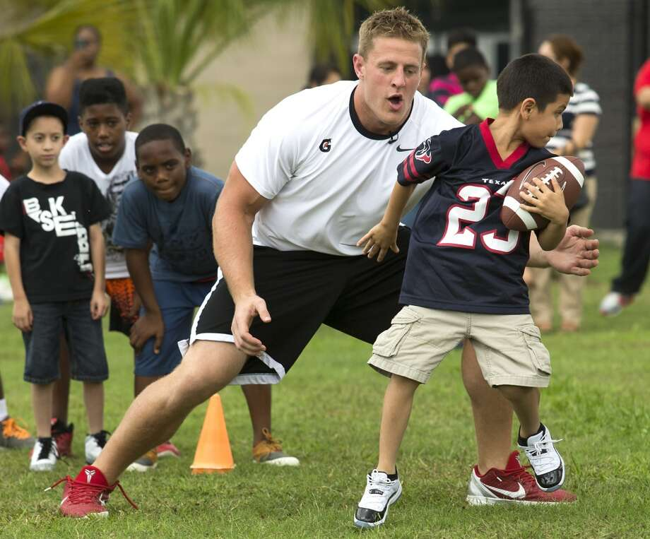 "J.J. Watt, left, lines up to ""tackle"" Charles Gonzales. Photo: Brett Coomer , Houston Chronicle"
