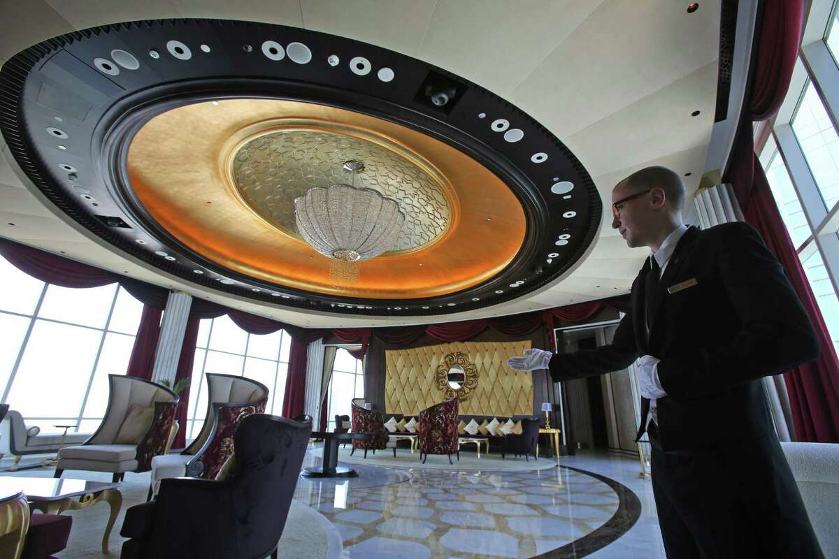 In this May 19, 2014 photo, butler Vido Kijne presents the guest welcoming pose in the Abu Dhabi Suite at the St. Regis in Abu Dhabi, United Arab Emirates. The nearly 24,000 square foot two-story suite, which sells for a nightly rate of $21,500, is suspended 720 feet above ground between the two buildings of the Nation Towers development. It has three bedrooms, a spa, a cinema, a bar area, two kitchens and a 360-degree panoramic view of the city, the islands, and the Sheikh Zayed Grand Mosque. The suite has 19 chandeliers made of Bohemian crystal, and an elevator that takes guests to ground level in total privacy, bypassing the rest of the hotel. (AP Photo/Kamran Jebreili) ORG XMIT: NYBZ261
