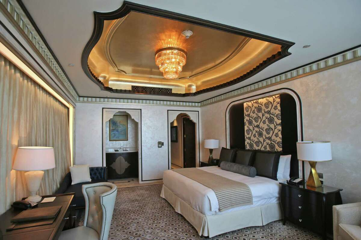 This May 19, 2014 photo shows one of the three bedrooms in the Abu Dhabi Suite at the St. Regis in Abu Dhabi, United Arab Emirates. The nearly 24,000 square foot two-story suite, which sells for a nightly rate of $21,500, is suspended 720 feet above ground between the two buildings of the Nation Towers development. It has three bedrooms, a spa, a cinema, a bar area, two kitchens and a 360-degree panoramic view of the city, the islands, and the Sheikh Zayed Grand Mosque. The suite has 19 chandeliers made of Bohemian crystal, and an elevator that takes guests to ground level in total privacy, bypassing the rest of the hotel. (AP Photo/Kamran Jebreili) ORG XMIT: NYBZ263
