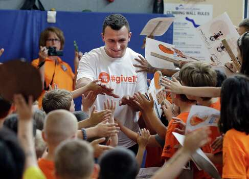 Cleveland Browns rookie quarterback Johnny Manziel is greeted by students at Grindstone Elementary school in Berea, Ohio Wednesday, June 4, 2014. The Browns 2014 rookies visited the school to kick off the NFL football team's community volunteer initiative. (AP Photo/Mark Duncan) Photo: Mark Duncan, Associated Press / AP