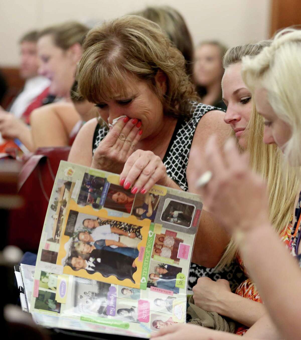Friends weep as they look at photo album of Michelle Warner, 31, before the start of closing arguments in a Houston courtroom.
