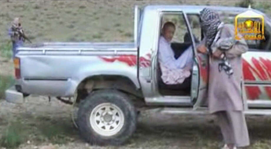 In this image taken from video obtained from Voice Of Jihad Website, which has been authenticated based on its contents and other AP reporting, Sgt. Bowe Bergdahl sits in a vehicle guarded by the Taliban in eastern Afghanistan. The Taliban have released a video showing the handover of Bergdahl to U.S. forces in eastern Afghanistan. The video, emailed to media on Wednesday, shows Bergdahl in traditional Afghan clothing sitting in a pickup truck parked on a hillside. More than a dozen Taliban fighters with machine guns stand around the truck and on the hillside. (AP Photo/Voice Of Jihad Website via AP video) Photo: Uncredited, HOEP / Voice Of Jihad Website