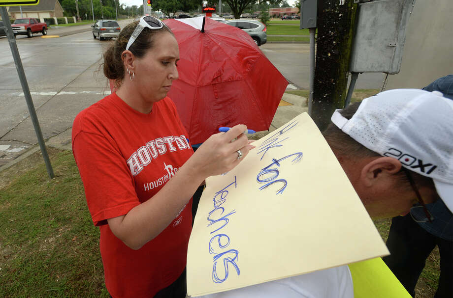 Danny McCurtain holds still while Julie Clinton creates a make-shift sign at Rogers Park on Wednesday. Several teachers and supporters gathered Wednesday at Rogers Park to protest the possible BISD layoffs directed at educators. Several cars passing by honked their horns and waved in support of the educators. Photo taken Wednesday, June 04, 2014 Guiseppe Barranco/@spotnewsshooter Photo: Guiseppe Barranco, Photo Editor