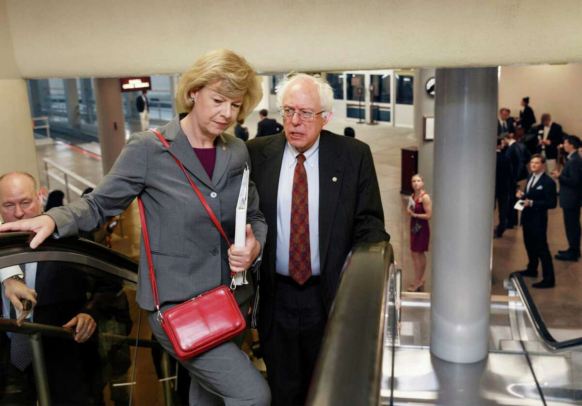 Senate Veterans Affairs Committee Chairman Sen. Bernie Sanders, I-Vt., right, speaks with Sen. Tammy Baldwin, D-Wis. as they take an escalator to the Senate on Capitol Hill in Washington, Wednesday, June 4, 2014. Sanders proposed legislation this week that would allow veterans who can't get timely appointments with VA doctors to go to community health centers, military hospitals or private doctors. The bill also would authorize the VA to lease 27 new health facilities in 18 states and give the VA secretary authority to remove senior executives within 30 days of being fired for poor job performance, eliminating lengthy appeals. (AP Photo/J. Scott Applewhite) ORG XMIT: DCSA108