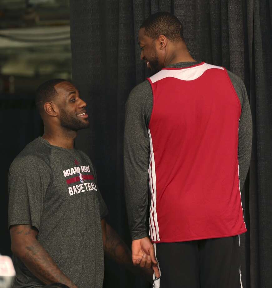 Miami Heat's Dwyane Wade, right, talks with LeBron James as he exits the stages during press conferences before practice at the AT&T Center, Wednesday, June 4, 2014. The Heat will play the San Antonio Spurs in the NBA Finals starting on Thursday. Photo: Jerry Lara, San Antonio Express-News