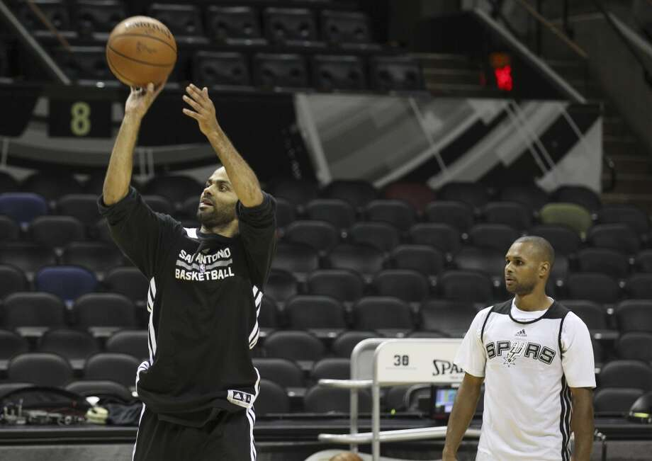Spurs' Tony Parker (right) shoots the ball with teammate Patty Mills during the NBA Finals practice and media session at the AT&T Center on Wednesday, June 4, 2014. The Spurs will play Game 1 of the Finals against the Miami Heat on Thursday. Photo: Kin Man Hui, San Antonio Express-News