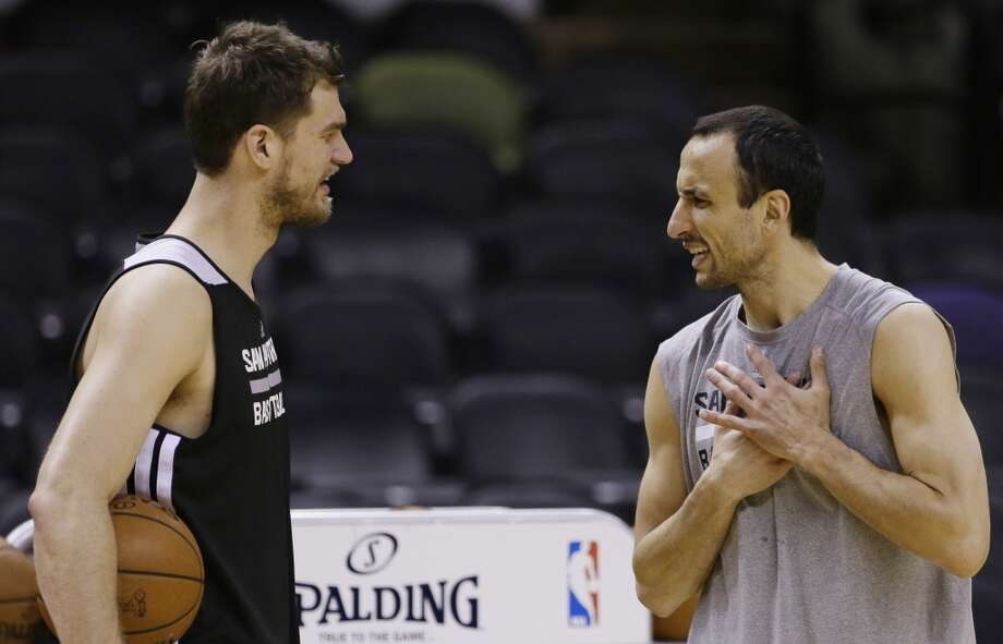 San Antonio Spurs guard Marco Belinelli, left, and guard Manu Ginobili talk during basketball practice on Wednesday, June 4, 2014, in San Antonio. The Spurs play Game 1 of the NBA Finals against the Miami Heat on Thursday. Photo: Tony Gutierrez, Associated Press