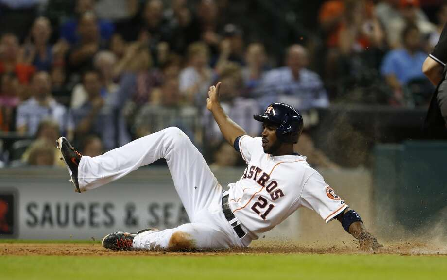 Astros center fielder Dexter Fowler slides home on an RBI single hit by  Jason Castro. Photo: Karen Warren, Houston Chronicle