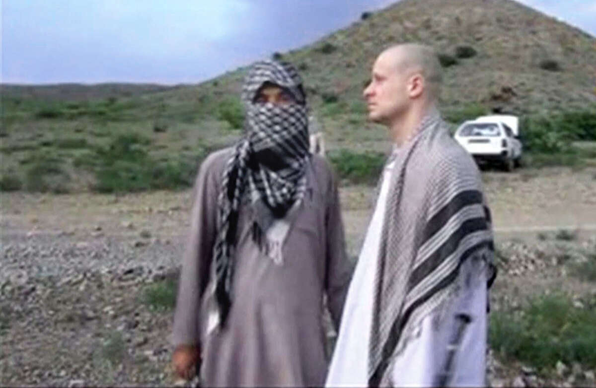 In this image taken from video obtained from Voice Of Jihad Website, which has been authenticated based on its contents and other AP reporting, Sgt. Bowe Bergdahl, right, stands with a Taliban fighter in eastern Afghanistan. The Taliban on Wednesday, June 4, 2014, released a video showing the handover of Bergdahl to U.S. forces in eastern Afghanistan, touting the swap of the American soldier for five Taliban detainees from Guantanamo as a significant achievement for the insurgents. Bergdahl was freed on Saturday after five years in captivity, and exchanged for the five Guantanamo detainees who were flown to Qatar, a tiny Gulf Arab country which has served as a mediator in the negotiations for the swap. (AP Photo/Voice Of Jihad Website via AP video) ORG XMIT: CAI118