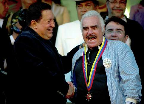 Venezuelan President Hugo Chavez (L) listens to Mexican singer Vicente Fernandez during a visit at the Miraflores presidential palace in Caracas, on September 12, 2012.  AFP   PHOTO/JUAN BARRETO        (Photo credit should read JUAN BARRETO/AFP/GettyImages) Photo: JUAN BARRETO, AFP/Getty Images / 2012 AFP